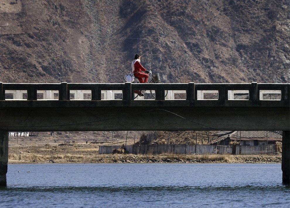 31. Девушка едет на велосипеде по мосту вдоль береговой линии реки Ялу